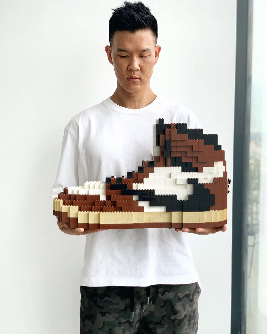 This image illustrates the work of artist Tom Yoo.A lego recomposition of the iconic 1985 Jordan 1 Chicago worn by Micheal Jordan.