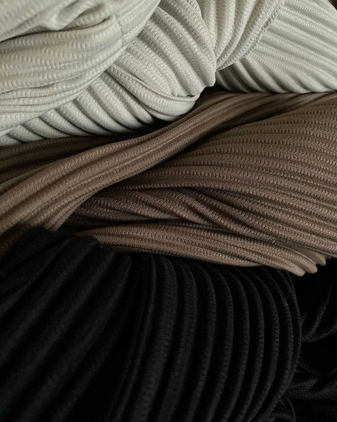 L'image représente des pantalons de la marque Homme Plissé par Issey Miyake. Les trois pantalons sont de tonalités de couleurs différentes avec du marron et du beige.