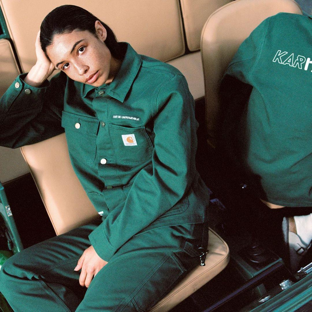 Mannequin portant une veste de travailleur verte issue de la collaboration entre la marque d'arthur Kar et la marque de streetwear Carhartt.