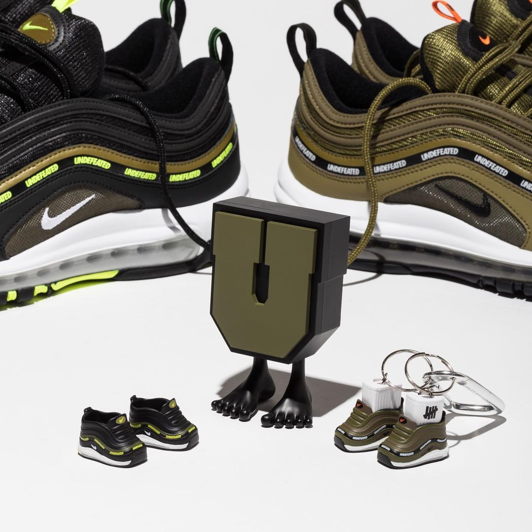 Two pairs of sneakers with some accessories at the front of the image. The sneakers are Nike's Air Max 1 in collab with Undefeated. The sneakers are camouflage green, black and lime. The soles are white and grey.