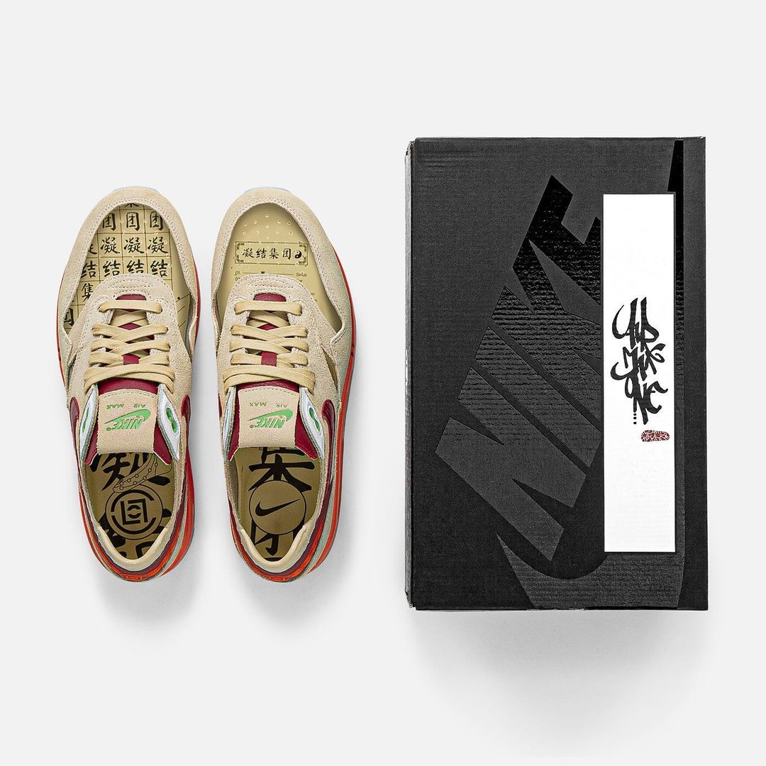 A pair of sneaker and a shoebox. The shoebox is matte and glossy black and feature a chinese calligraphy. The sneakers are Nike's Air Max 1 in collaboration with Clot. The shoes are beige, red with a light touch of green. The shoe is transparent on the top. You can see chinese calligraphy on the inside.